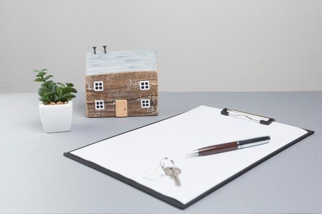 casa-modelo-llaves-portapapeles-sobre-superficie-gris_23-2148203975